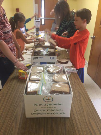 Children packing sandwiches for homeless