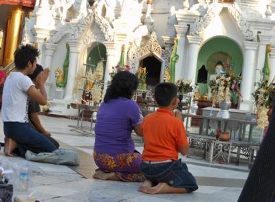 People kneeling on prayer mats