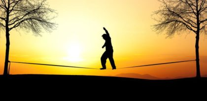 Man on tightrope at sunset