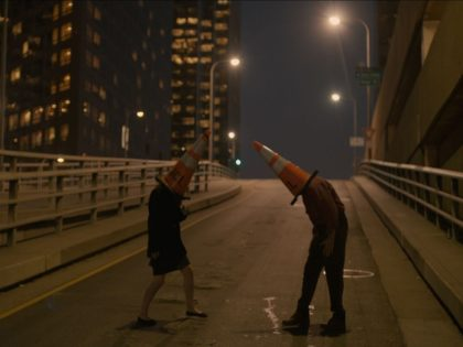 People wearing traffic cones