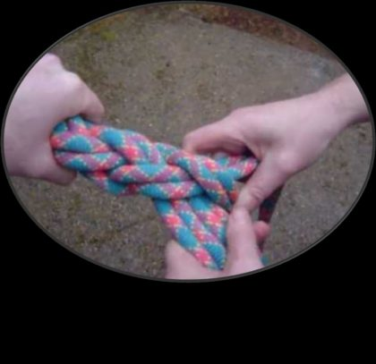 Hands knotting rope
