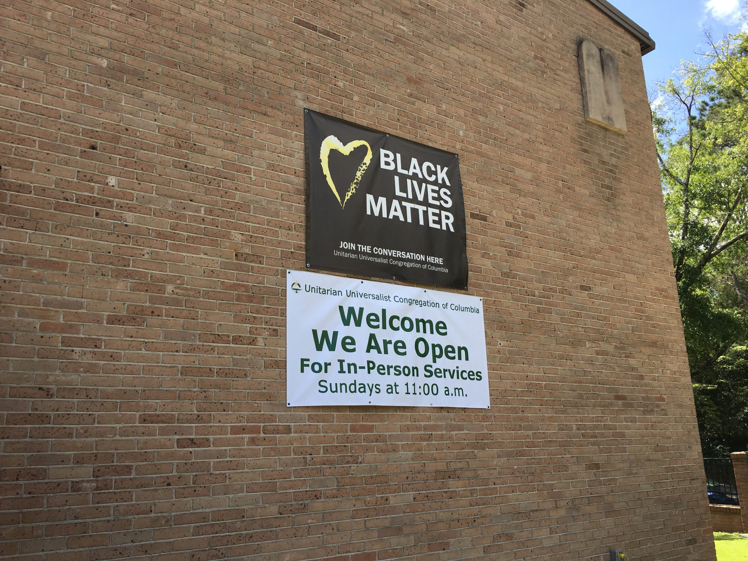 Black Lives Matter and Reopening signs on side of building